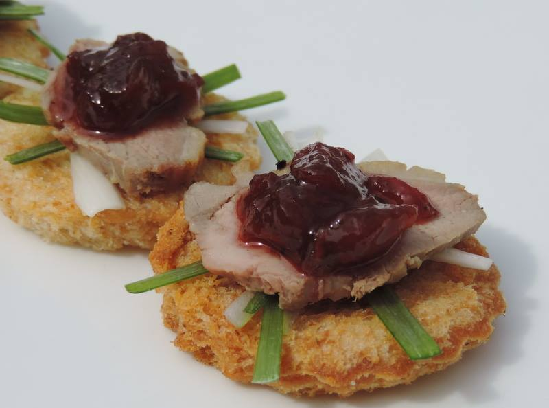 Seared duck on a crisp crouton with spiced plum chutney and spring onions