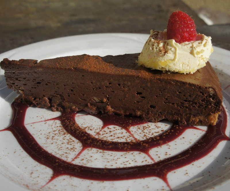 Rich chocolate mousse tart with raspberry coulis