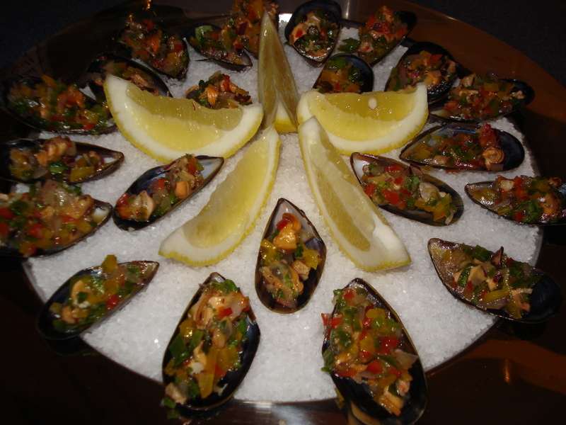 Mussels with garlic, fresh tomato and peppers on a salt bed