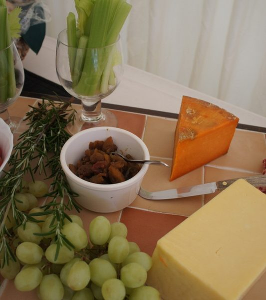 Cheeseboard with grapes, celery and chutney