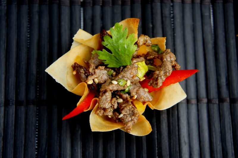 Beef strips in soy, ginger and chilli in afilo basket with fresh coriander